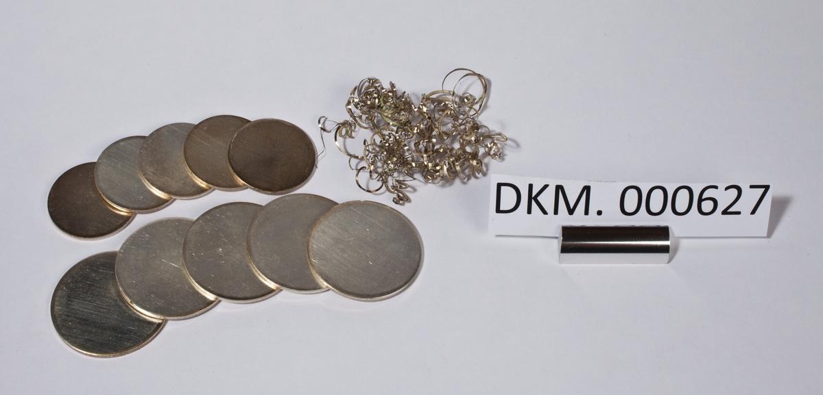Ti runde, små sølvplater i ulik størrelse og sølvspon.