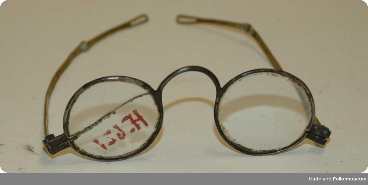 Briller; runde glass med jerninnfatning og messingstenger. Stengene er todelte og har hull til brillesnor i endene. HF-nr er skrevet på glasset.