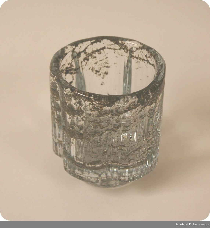 Lav sokkel. Sylinderform med fem buer i godset. Riflet overflate. Tykt gods
