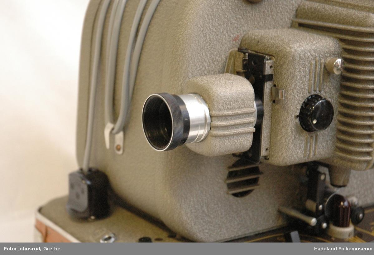 Filmrull og høyttaler henger i overdelen av kassen.