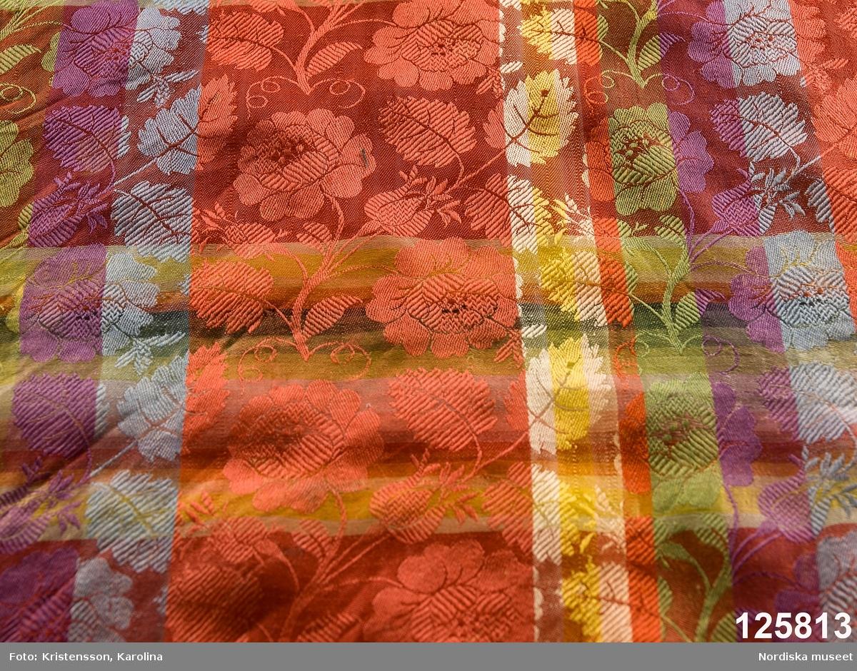 """Kvadratiskt halskläde av siden, klarröd botten med rutor i grönt, ljusblått, ljuslila och gult med ett yttäckande invävt mönster, troligen med jacquard, med slingrande rosor. Kantbård med """"päronlika"""" blommor/frukter som på 2 mötande sidor är gröna och på de 2 andra vita. Upprispad kort frans på alla sidor. I ena hörnet en tydlig svart rund stämpel med texten: Stockh. hallstemp 1839. Anm. Stor fläck i två av hörnen. /Berit Eldvik 2011-11-11"""