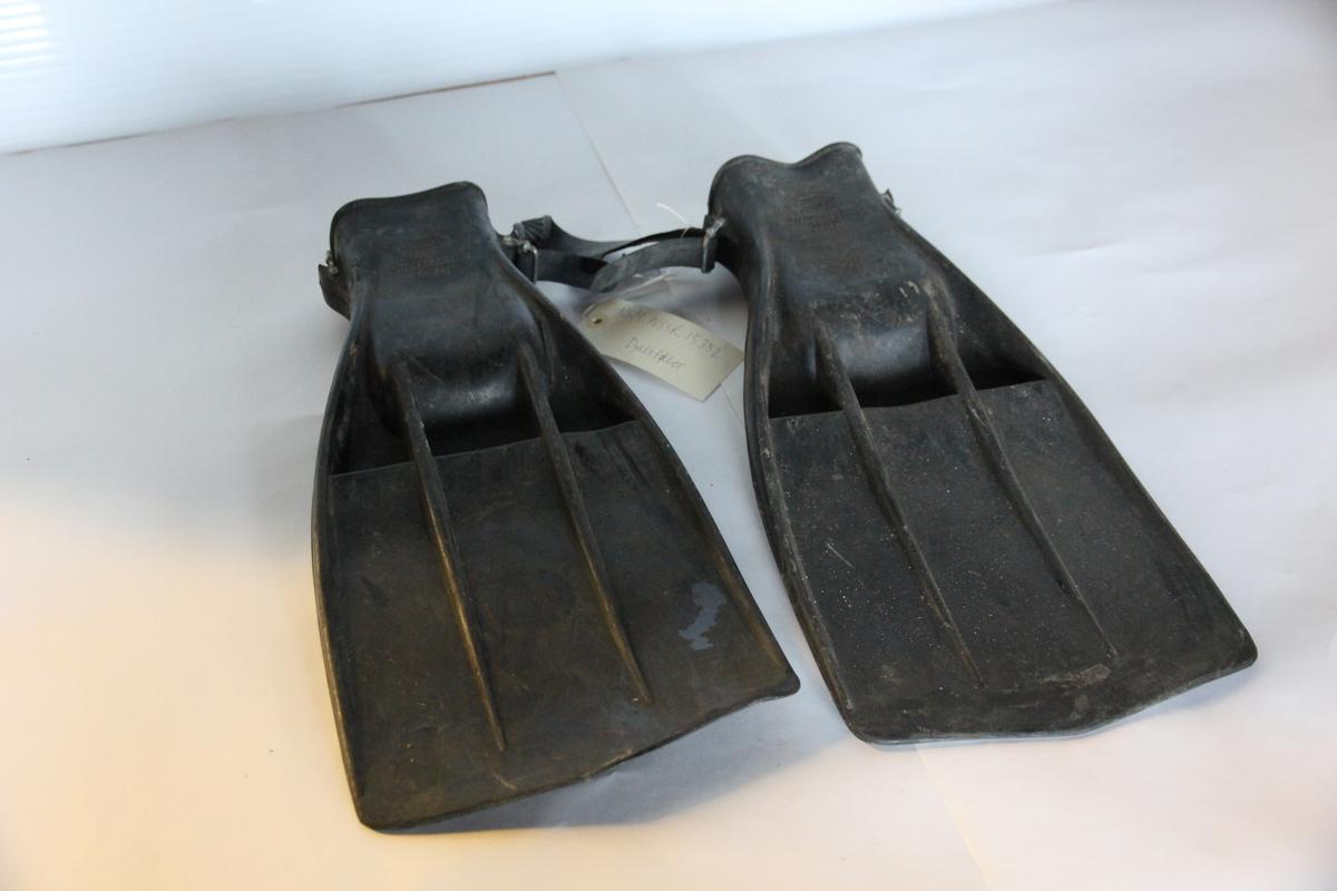 Et par dykkerføtter av svart gummi med stålspenner.