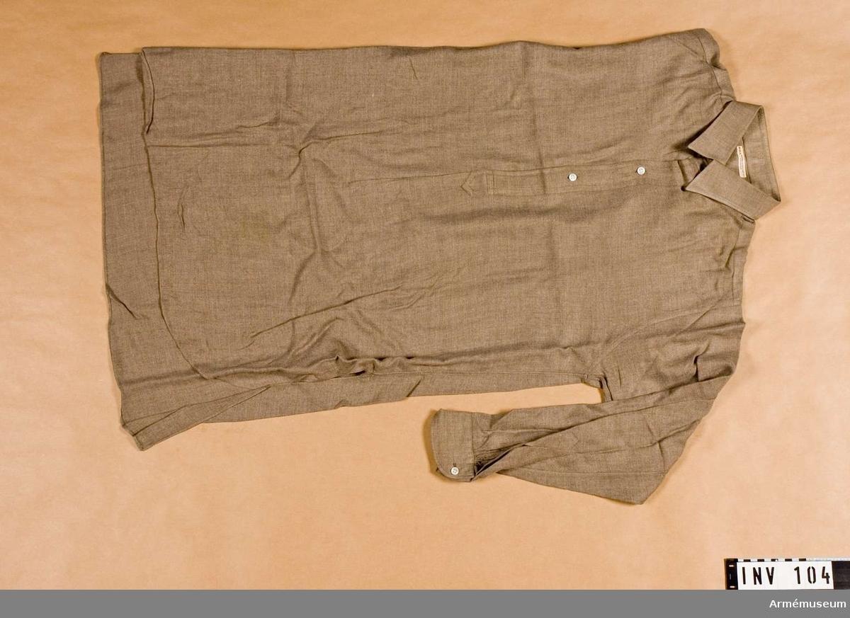 Skjorta m/1939, Generalitet. Skjorta av gråbrungrönt ylle. 390 mm långt sprund framtill som knäppes med tre pärlemorknappar. Skjortan har dubbelvikt krage med rundade hörn. Långa ärmar med manschett som knäppes med vit pärlemorknapp.  Samhörande gåvor AM.000001 - AM.000119.