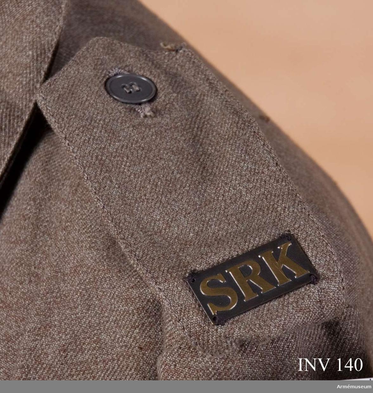 Axelklaffen är försedd med knapp (15 mm) placerad på undre delen och knapphålet placerat på övre fliken. SRK i gulmetall  upphöjd på mörk metallplatta. Mått: hel längd (vikes dubbel)  235 mm, bredd vid vikning 43 mm, bredd vid snibben 55 mm, bredd  vid undre snibben 27 mm, metallplatta 32 x 15 mm, bokstäver 11  mm höga.