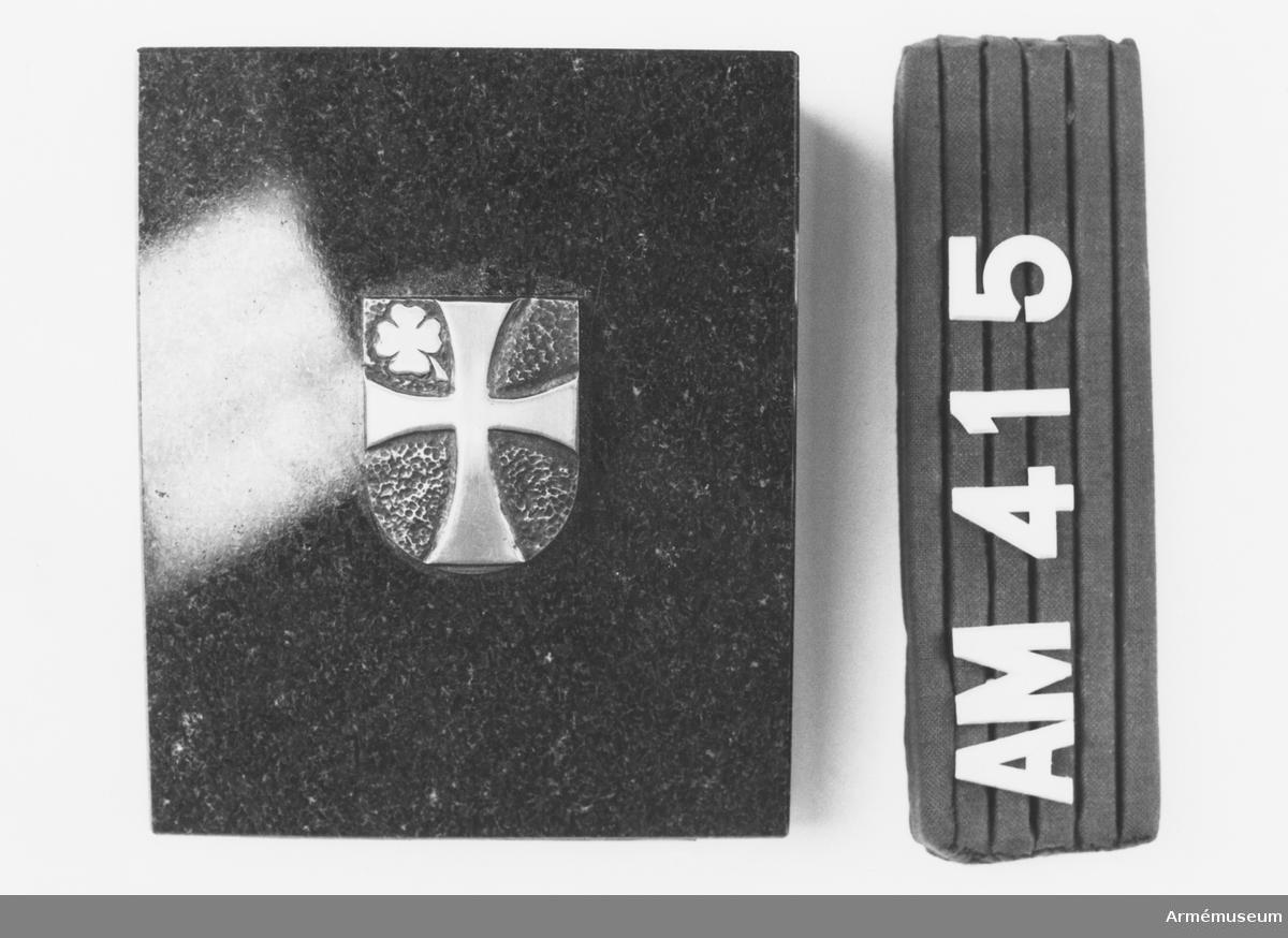 Samhörande nr är 294-299, 321-350, 400-448. Emblem, minnesgåva från 3. Pz.Gren.Brigade. Sten och emblem från 3. Pz.Gren.Brigade, mottagen av CA under besök vid västtyska armén maj 1972. Av svartmellerad marmor. I mitten ett emblem i silversmide. På hamrad silverbotten, mörkt polerad, ett kors i slätt silver och en fyrklöver i övre vänsterhörn. Längst fram på kanten av stenen graverat i silverplåt: 3. Pz.Gren.Brigade. Plattans längd: 70 mm, bredd: 15 mm. I botten är stenen klädd med grön filt.