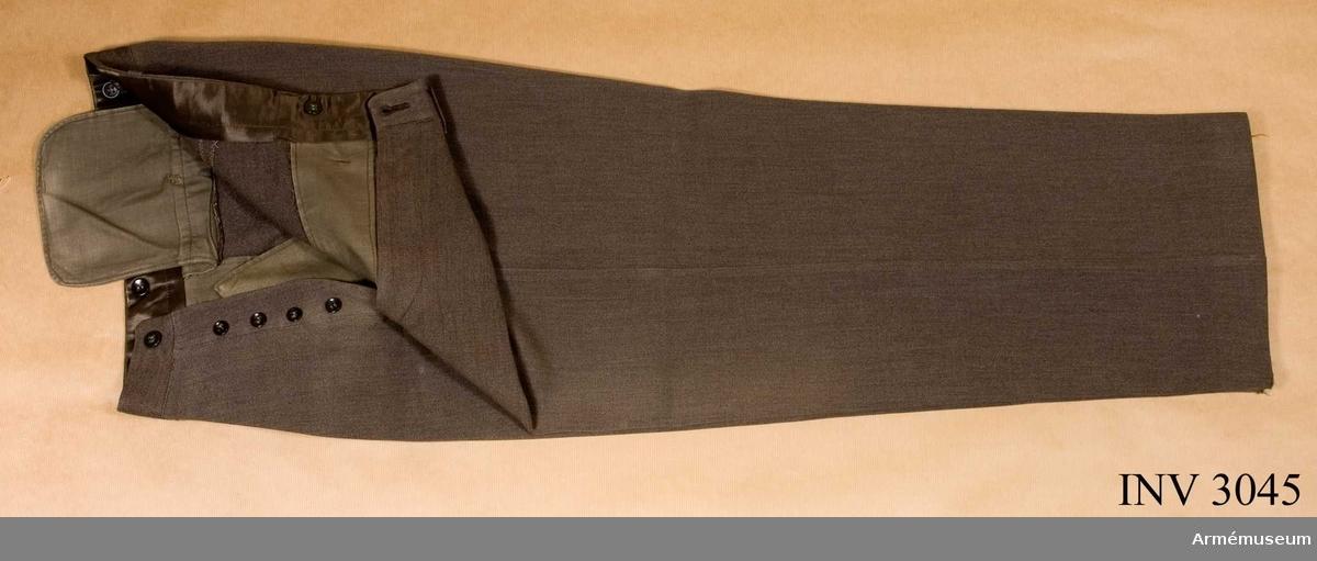 Stl B 50. Av gråbrungrön diagonal med raka ben. Julpknäppning med fem knappar. Linningen är skodd med brunt foder. Har sex knappar på insidan för hängslen. Utanpå finns sex hällor för livrem. Två sidfickor. En passpoalerad bakficka som knäpps med knapp. Bäres till vapenrock. Överste A Hallström var ställföreträdande militärbefälhavare vid II milo 1958.