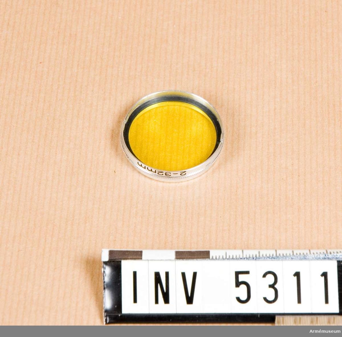 Gulfilter, M 1942-30044.  Gulfilter användes för att tona ner en blå himmel vid svartvit fotografi. Gula och gröna föremål återgives ljusare. Detta filter är avsett för Agfa Silette kameran.  Samhörande nr är AM.5312 (fodral).