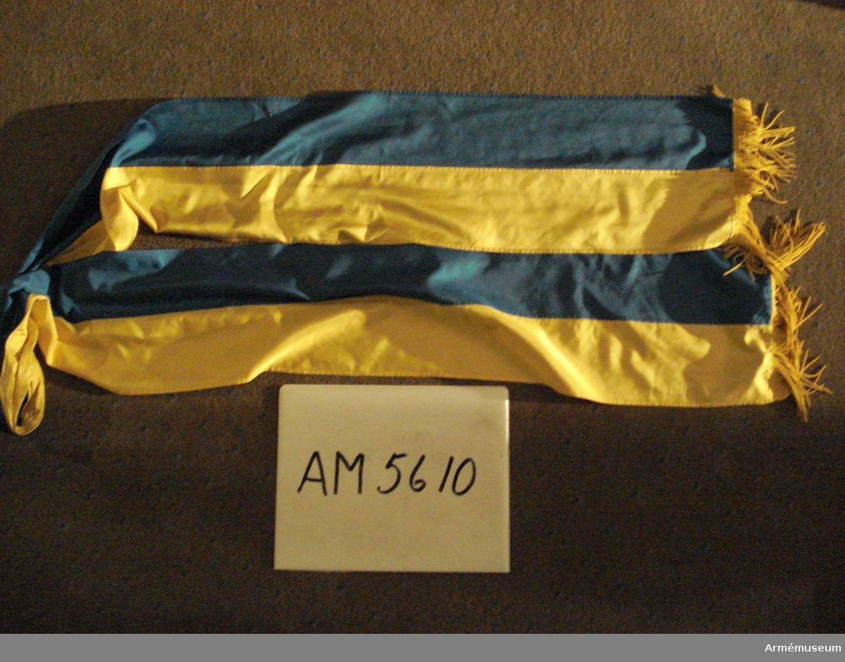 Fanband av diagonalvävt natursiden med halva bredden blå och halva gul. Avslutad med silkefrans i båda kortsidor.