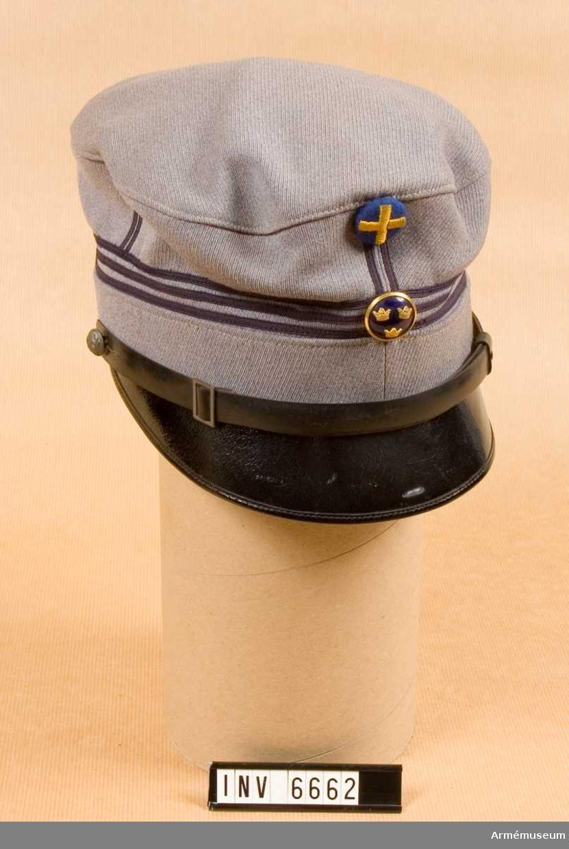 Framtill blåemaljerad knapp m/1965 och broderat  landstormsmärke i gult silke på blå botten, samt stolpar och  gradbeteckning av mörkblått silke. I detta fall är  gradbeteckningen tre band, beteckning för kapten. Svart lackerad läderskärm och mössrem med spänne och knäppt med  landstormens lilla knapp. Storlek: 55. Mössan är i kullen märkt: NH Peterssons Nya Hattmagasinet Göteborg Korsgatan 24.