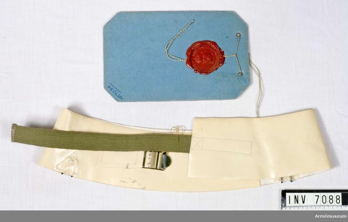 """Av vit plastbelagd väv, och med grön textilrem och spänne av svart metall. Fästes runt hjälmen.  På vidhängande modellapp står följande text: """"Dnr 239 UtrB, Modell å Trafikhjälmband m/54, fastställd av chefen för arméförvaltningen  Generallöjtnant C A Ehrensvärd, Stockholm den 26. januari 1954. I. Modigh Byråchef."""""""