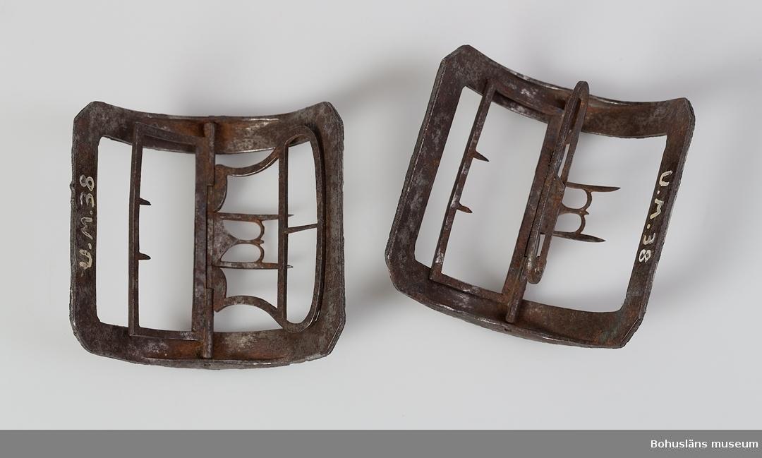 Ett par kraftigt bågformiga skospännen, troligen från den gustavianska eran. Spännen av järn vars översida har fått ett gjutet dekorerat skikt utav en legering av vitmetall.  Blånerade delar på båda metallsorterna. Lätt rost på järndelarna. I övrigt hela. G:29 i 1869 års tryckta katalog.  Ur handskrivna katalogen 1957-1958: Skospännen av stål Mått c:a 7,5 x 7,5 cm. Stål m. bred ornerad ram. Rostiga. Spännena hela.  Lappkatalog:78