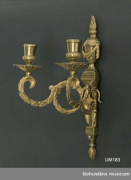 Ur handskrivna katalogen 1957-1958: Ljusarmar, mässing H.: 32 cm Tvåarmad. Ljusarmarna utgående från ett pelarformat stycke m. urna. Föremålet är helt. Från början av 1800-talet.  Lappkatalog: 90