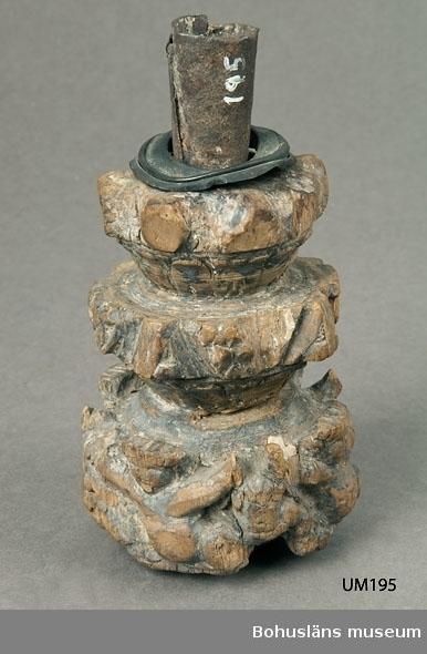 """Ur handskrivna katalogen 1957-1958: Ljusstake, järnbleck trä Bottendiam: 7,7. H: 15. Föremålet något skadat. Figurer utskurna i träet.  Kompletterande katalogisering i oktober 2008. Trädel som sekundärt har gjorts om till ljusstake.  Ljusstake i tre våningar. Svarvat, skulpterat trä i ett träslag som ev kan vara valnöt.  Fyra formade keruber på nedersta nivån, mellersta delen har bl a skulpterade blommor med fem kronblad. Översta nivåns former är såpass skadade att det inte syns vad det har varit. Nästan halva """"insnörpningen"""" mellan nedersta nivån och mellersta är genomsågad.  Rester av svart färg på delar av objektet; ovanpå det mörka färglagret ligger i band/linjer/bårder på vissa delar en ockragul  färg med rester av förgyllning. Ett tunt lager vax eller stearin på ytan, på något ställe samt i pipan fläck respektive klump av ett dylikt material.  I det svagt välvda området undertill, det som betecknas som botten, finns ett hål som visar att delen suttit samman med ytterligare någonting. Ljusmanschett av mässing där också syns rester av förgyllning. Pipa av järnplåt/-bleck."""