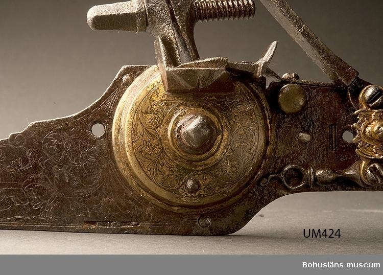 Pistollås från tidigt 1600-tal tillverkat i Tyskland. Förgyllt graverat hjullås. Typen förekom på Sachsiska officerspistoler från tidigt 1600-tal. Hanen är en senare komplettering.  På vidhängande äldre etikett antecknat 1916 av Knut Adrian Andersson, intendent Uddevalla museum: Hjul-lås av skjutgevär från 1500-talet. Detta bösslås skänktes till U-a museum 1862 av Herr Mellbin å Sundsby (Tjörn) Bohuslän.  I 1869 års katalog G:51 antecknat som Äldre skjutgevärslås  Ur handskrivna katalogen 1957-1958: Hjullås, Tjörn L. 33,5 cm; av järnm. 2 delar av förgylld brons; (1500 -t.?) Ngt rostigt.  Lappkatalog 55