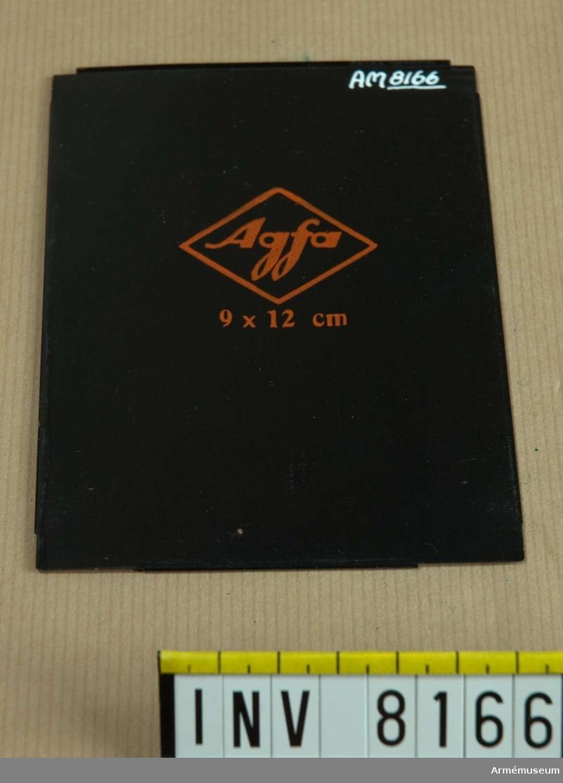 Samhörande nr är AM 8151 - 8199. En romb ringar in ordet Agfa och under romben står 9 x 12 cm - allt står med orange text på svart bakgrund.Inlägget placeras i en kassett avsedd för plåtar vid fotografering på bladfilm. Ur fotomaterielsats 7 för Brückner resekamera.
