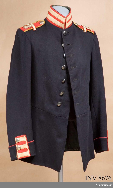"""Tillverkad i mörkblått kläde med vadderat foder. Släta silverknappar och röd krage, axelklaffar och ärmspeglar. Ärmspeglarna har tre s k knapphål i vit redgarn och ärmens uppslag kantas med en röd passpoal, även fickorna. Kragen har två """"knapphål"""" av vitt redgarn och axelklaffarna är försedda med konung Gustaf V:s namnchiffer i silver och är försedda med ett s k studentsnöre runt kanten (gult och blått). Vapenrocken är buren av apotekare Ivar Eriksson, Västerbotten, år 1907 som studentbeväring vid Göta livgarde I 2."""