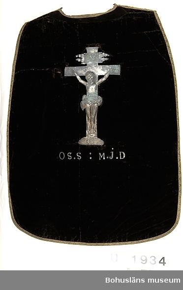 """Mässhake från Uddevalla kyrka i svart bomullssammet kantad med band av förgylld metalltråd; krucifix i silverplåt eller försilvrad (förgylld?) plåt på ryggsidan. Fodrad med ett mörkt brunt glättat linnetyg.  Mässhaken är troligen tillverkad på 1740-talet. Krucifixet har lossnat och förvaras separat.  Pålött på krucifixet """"INRI"""" och """"O.S.S.:M.J.D. ANNO.1745."""" Krucifixets mått 51,0 x 29,7 cm. Påsydda metallbokstäver under krucifixets plats: """"O.S.S : M.J.D"""" På framsidan en liksidig spets knypplad av metalltråd och silke-/linnetråd; monterad längs halsöppningen och en bit ner. Längd 60 cm. Delar av sammetstyget så sliten att det lagats/bytts ut mot en brunsvart sammet med mattare karaktär.  Enligt Marie-Louise Franzén, Statens Historiska museum, Stockholm i december 2002: Mässhakar av denna typ är ovanliga i Sverige. Det finns mycket få bevarade. I Historiska museets samlingar finns inte någon enda mässhake från Bohuslän.  Ur handskrivna katalogen 1957-1958: Mässhake, U-a kyrka H. 106 resp. 123 cm. svart sammet, silverstickn. krusifix i försilvr. plåt; mont. som föreg.(UM1933).  ramen: 139,5 x 106 cm. O.S.S.:M.J.D. år 1745.  Lappkatalog: 12"""