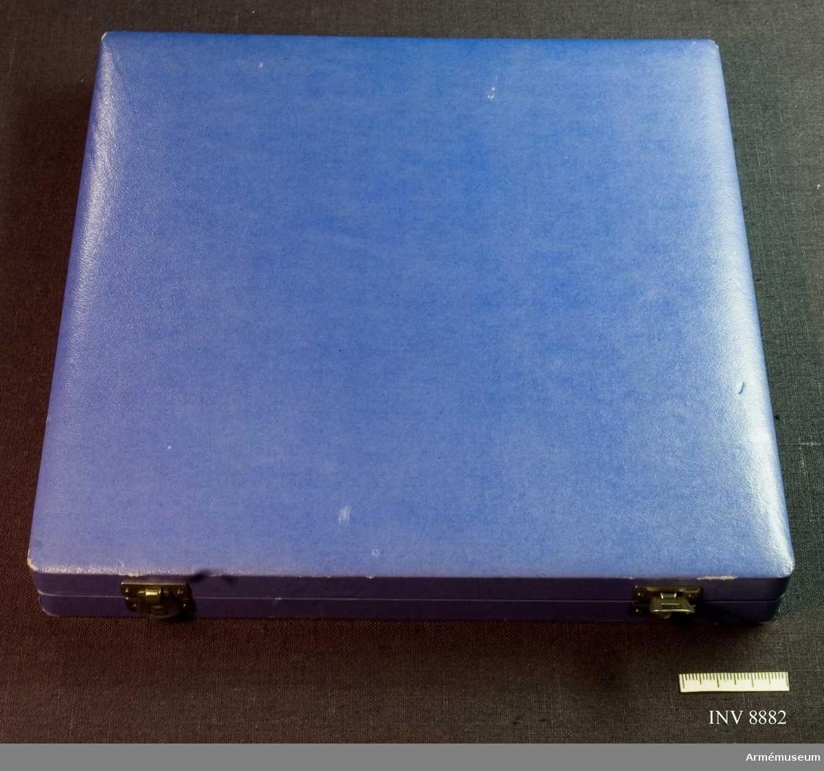 Längd 220 mm. Bredd 215 mm. Höjd 215 mm. Ett blått läderimiterat etui med två silverfärgade spännen. Det är klätt inuti med mörkblå sammet med försänkning för medaljen. Lockets insida är klätt med vitt siden och märkt med guldskrift C C Sporrong & CO Stockholm.  Samhörande nr är AM.8881-8882