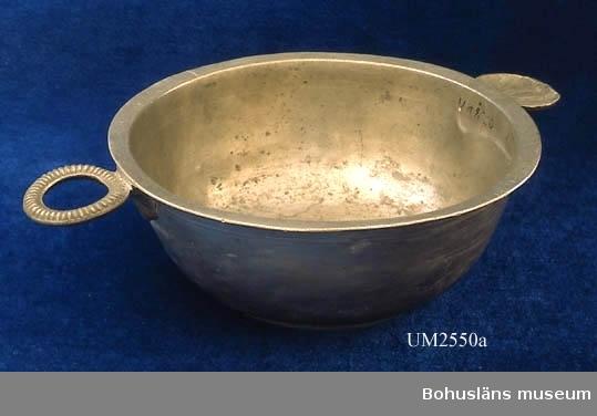 """Föremålet visas i basutställningen Uddevalla genom tiderna, Bohusläns museum, Uddevalla.  Rund matskål av tenn med utvikt kant. Ett snäckformat och ett genombrutet handtagsöra, en godronnerad ring. Låg fotring. Trestämplad  botten med mästarstämplar """"E M H"""" i separata rektanglar med avskurna hörn. Årsbokstav  """"I 2""""; 1791. Stadsstämpel saknas.  Tillverkad av Eric Magnus Hammarstrand (1753-1837), tenngjutare i Falun 1788-1837.  Ur handskrivna katalogen 1957-1958: Såsskål Mynningsdiamet.: 16 cm. H.: c:a 6 cm. Tenn. Två små handtag, det ena snäckformat, det andra i form av en ring. Föremålet helt. Tillverkad i Falun av tenngjutare Hammarstrand 1791.  Lappkatalog: 58  Litt: Bruzelli, Birger: Tenngjutare i Sverige. Forum 1967."""