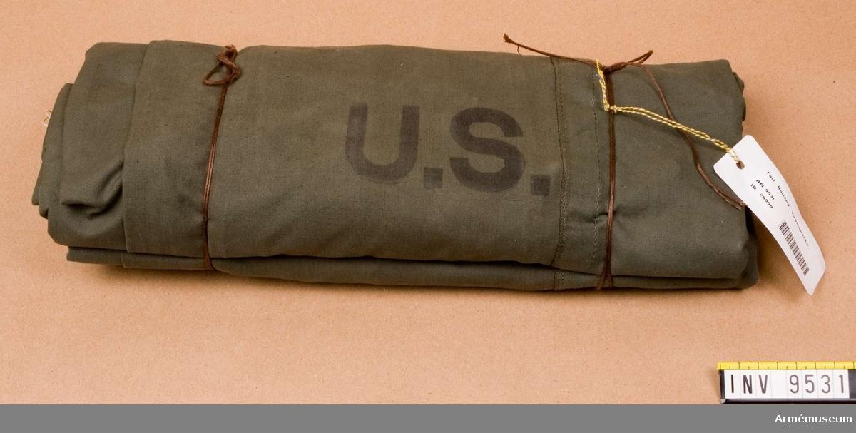 Av olivgrönt tyg med vita bomullsrep. Märkt U.S. Gåva från FMV.