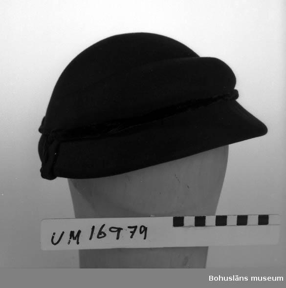 """Svart formpressad hatt. Prydd med svart sammeband.  Isydd band med text: """"Modeaffär Ester Lundell Lysekil tel 319."""""""