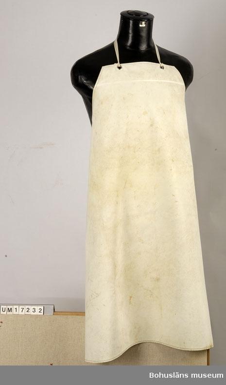 """Förkläde av vit  vävburen plast. Snoddarna iknutna i metallögletter, gulfläckiga.  Använt av kvinnlig anställd inom konservindustrin.  AB Elis Luckeys Konservfabrik grundades i Lysekil 1893 och hade en filial i Danmark från 1933. Vid årsskiftet 1978-1979 förlades all sillinläggning till Danmark och all burktillverkning till Lysekil. Hösten 1980 stängdes Lysekilsfabriken helt, och snart därefter även Danmarksfilialen. Ett av firmans kända märken var """"Brottsjö"""".  Vid båda fabrikerna hade man såväl sillinläggning som bleckärlstillverkning.  AB Elis Luckeys Konservfabrik var en av tre fiskkonservföretag som inför nedläggningen dokumenterades av Bohusläns museum under 1979. De andra företagen är AB Gust. Richter och Export AB Franz Witte & Co., båda Lysekil.  Samtidigt förvärv: UM17232 - UM17394, UM18076-UM18120, UM24155-UM24156, UM24186-UM24188 samt UM31292 - UM31293.  Materialet utgör en samlad gåva från Cai Luckey, Lysekil, sonson till grundaren av företaget, AB Elis Luckey. Från samma givare även UM15081:1-41  Se även tidningsartikel om sortimentet i Bilagepärmen, UM15081 samt interiörbilder, UMFA53829, Luckeys konservfabrik.  Bohusläns museums arkiv: Fotografier, intervjuver, samtals- och observationsanteckningar i samband med dokumentationsprojekt 1979.  Litt: Konservindustrin. Bohusläns samhälls- och näringsliv. Bohusläns museum, Etnologiska institutionen vid Göteborgs universitet. 1983."""