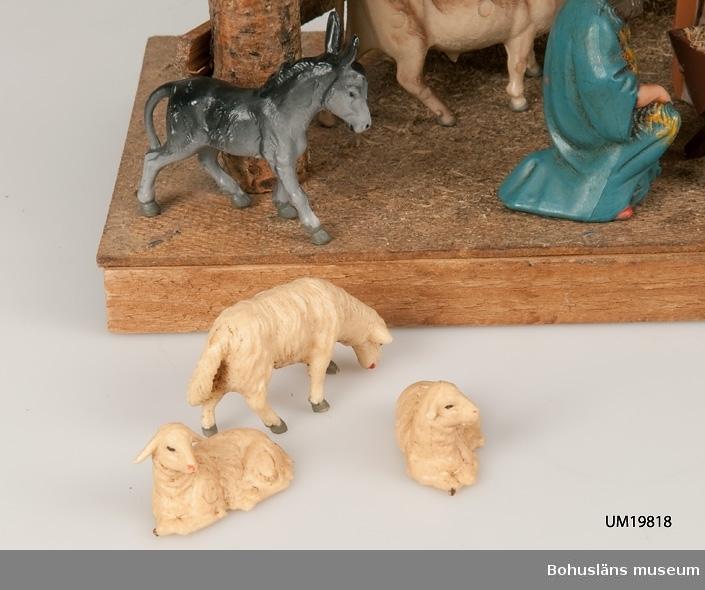 Stall med halmtak, trästolpar samt golv och vägg av masonite. Märkt UM19818:1 18 st figurer tillhör julkrubban. De är märkta UM19818:2. Krubba, Jesusbarnet, Maria, Josef, en herde, de tre vise männen, en åsna, en oxe, tre liggande får, fem stående får varav ett betydligt större. En av de tre vise männen märkt: Germany Elastolin brukar denna typ av plastisk massa benämnas - egentligen ett  tyskt inregistrerat varumärke på en kompositmassa.