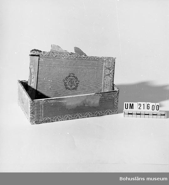 594 Landskap BOHUSLÄN  Förvaringslåda för 6st rakknivar UM21601-21606 samt strigel UM21607. Asken klädd med pappersimitation av plywood.  UMFF 36:4