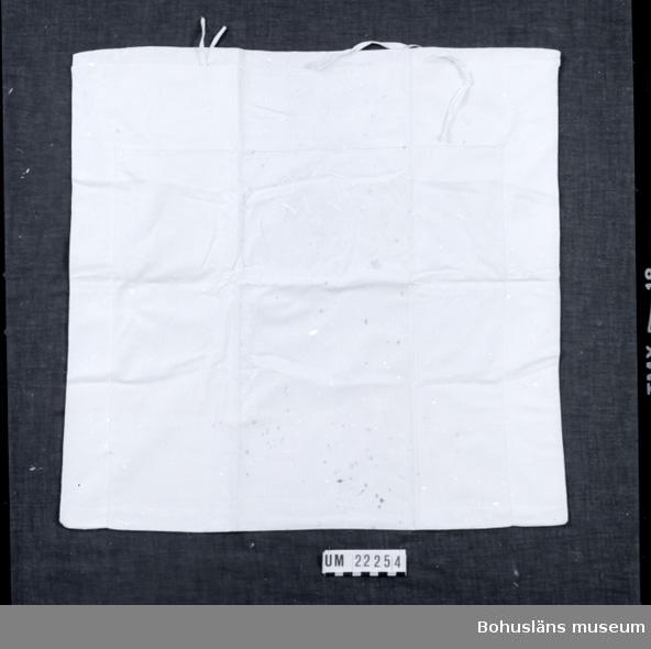594 Landskap BOHUSLÄN  Örngottet är sytt av vitt bomullstyg, med band för knytning. Tyget har rostfläckar.  UMFF 93:12