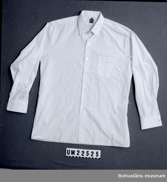 """410 Mått/Vikt ! ÄL 53, KRA 4 CM 594 Landskap BOHUSLÄN  Vit, med bröstficka på vänster sida. Enkla manschetter, varav den vänstra är söndernött. Sydd etikett i nacken med texten: """"Epa Las Vegas stryk- [..] % polyester 35% bomull. 41. import.""""  UMFF 111:6"""