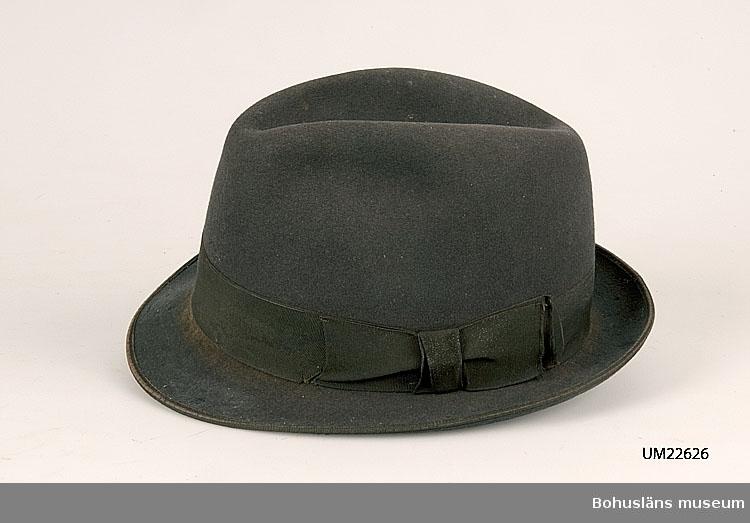 """410 Mått/Vikt ! BRÄTT B 4 CM 594 Landskap BOHUSLÄN  Hatten är tillverkad av grå filt. Kullband och kantband av rips. Hatten har små brätten och svart sidenfoder. Med följande text: """"Fribergs Uddevalla"""". Insektsangripen.  UMFF 117:9"""