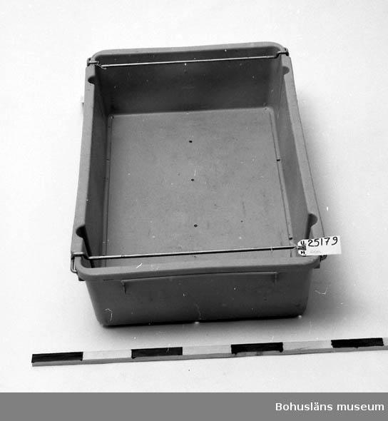 594 Landskap BOHUSLÄN 503 Kön MAN 394 Landskap SKÅNE  Grå rektangulär låda. Metallstänger på kortsidorna som är rörliga. Stängerna fälls inåt när en annan låda skall stå ovan på så att den vilar stadigt. Hål för avrinning av vatten i botten. Inventerad 1996-11-18 GH.