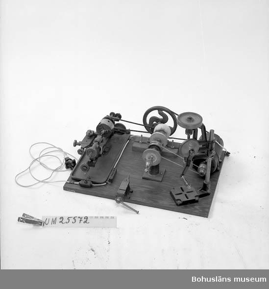 Svarv av bordsmodell som av ägaren ihopmonterats av olika delar och monterats på en träplatta jämte borr och skruvstöd. Använd av ägaren vid tillverkning av material för ljudinspelningar.