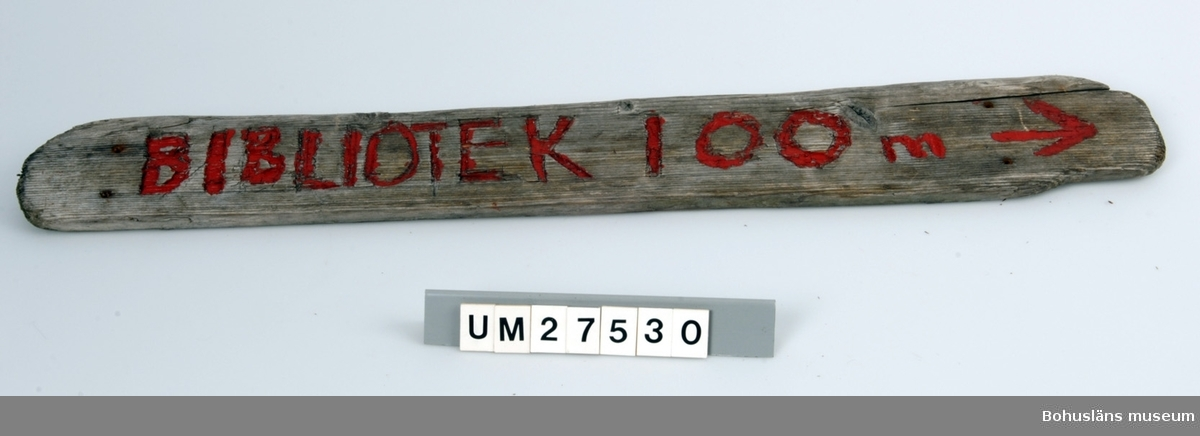Vägskylt tillverkad av elev vid Åstols skola, Tjörns kommun. Vägskylt  tillverkad av en bit drivved. På framsidan inhuggna texten BIBLIOTEK 100 m, målat i rött samt en pil som pekar åt höger.  Borrhål för skruvar.  Föremålet visades i utställningen Moderna skärgårdsbor på Bohusläns museum 2002. Utställningstext: Vägskyltar Nio skyltar som vägvisare på Åstol.  Från affären till rökeriet är det 375 meter och från skolan till badplatsen är det 200 meter. Skyltarna berättar om en liten ö med många mötesplatser. Här finns affär, bibliotek och skola - restaurang, lekpark och flera församlingar. En tätbebyggd ö omgiven av havet, med skolan i centrum - så viktig för barnfamiljerna och åretruntboendet. Skyltarna är gjorda av elever i årkurs 4 - 6 på Åstols skola.  Skylten ingår i insamlingen i projektet Moderna skärgårdsbor, UM27511 - UM27595 och kommer från Åstol.   För övrigt material från Åstol, se UM27524-UM27538 och UM27566-UM27594; UM27524 Tjörn Runt-teckning UM27525- Vägskyltar, 9 st UM27533 UM27534:1-2 Eternitplattor, 2 vita refflade  UM27535 Eternitplatta, 1 vitmålad slät UM27536:1-2 Eternitplatta, 2 gröna UM27537 Cykelkärra UM27538 Matjordsäck, 2 st (omärkt) UM27566- 28 barnteckningar över Åstol, indiv. inv.nr. UM27593 UM27594 Skylt frikyrkan med gudstjänstaffisch Arkivet 9 uppsatser från skolbarnen i samband med teckningarna.  För information om projektet Moderna Skärgårdsbor, se UM27511.  Litt: Sjöholm, Carina. Moderna skärgårdsbor i gammal kultur. Skrifter utgivna av Bohusläns museum och Bohusläns hembygdsförbund nr 73. Bohusläns museums förlag.  Avsnittet om Åstol s. 17 - 45..
