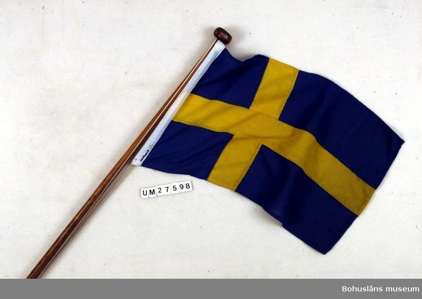 Akterflagg  - svenska flaggan -  i bomull på lackad mahognystång med knopp för fastsättning i aktern på snipan Lisen (UM27596). Med flagglina av nylon. Båten visas i Båthallen, Bohusläns museum.  För uppgifter om båten och förvärvet, se UM27596.  Se uppgifter under Placering.