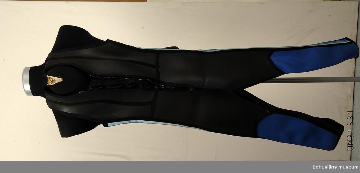 410 Beninnerlängd 67 cm Ärmlös våtdräkt med långa ben i svart och blått. Kroppsnära modell med kraftig plastdragkedja fram och en längs vardera underbenen. I nacken etikett med texten CAMARO ANZÜGE, damstorlek 40. Sydd av värmehållande, tjock neoprene, på utsidan med gummerad, svart yta.  På kroppsidorna är neopremytan randad i tre blå färger. Modellen är skuren av många små delar, sammanfogade med maskinsömmar, på utsidan förstärkta med svarta band.