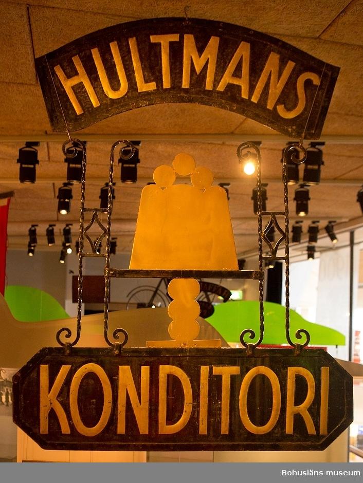 """Föremålet visas i basutställningen Uddevalla genom tiderna. Konditoriskylt av målad och pressad plåt i två delar, likadan på båda sidor. Svartmålade skyltar med texten HULTMANS KONDITORI i guld på varsin skylt över och under ett bakverk på hög fot. Arrangemanget hålls samman av stela vridna järntenar i konstrikt mönster. På en äldre bild kan man se att skylten varit fästad i en skyltgalge och suttit rätvinkligt ut från husväggen så att den kunde ses från båda håll.  1924 öppnade  Bernt Hultman konditori på Kilbäcksgatan 7 i Uddevalla. I gårdshuset låg bageriet. Konditoriet övertogs av systrarna Ingeborg och Gullan Hultman som drev verksamheten till slutet av 1960-talet. På 1960-talet frekventerades konditoriet av unga studerande herrar vilka senare slöt sig samman i föreningen Hultmans Vhenner.  Längs gatan låg också bl.a. en textilaffär och en glas- och ramaffär.  Fastigheten revs 1973 och ersattes av en vederstygglig byggnad och en parkeringsplats som ännu misspryder staden med ett trist  gatuparti som länge har kallats stadens skamfläck.  Sedan bildandet 1965 har medlemmar i föreningen Hultmans Vhenner arbetat för att gränden vid nedre delen av gatan skall få namn efter konditoriet. 2009 godkände slutligen kommunfullmäktige oväntat förslaget.  Föreningen har också gjort sig känd för att årligen dela ut ett kulturstipendium på 5.50 i ostämplade frimärken till förtjänta Uddevallabor """"såframt inte kulturskymning råder"""".  2003 donerade yrkesskollärare Allan Hell överdelen av konditoriskylten till föreningen och senare blev skylten komplett tack vare bageriföreståndade Bernt Isaksson som  räddat  nederdelen från skrotning. 2003 erbjköds museet skylten som gåva. I april 2006 överlämnades skylten officiellt under högtidliga former till Bohusläns museum och visas i basutställningen Uddevalla genom tiderna.  Se Bilagepärmen UM31528 för utskrift av det högtidliga tal som avhölls i samband med överlämnandet av konditoriskylten till Bohusläns museum, tidningsartiklarna nedan"""