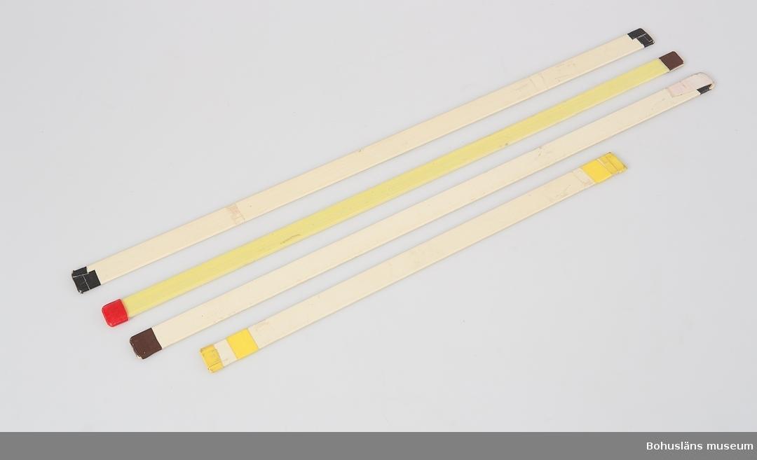 Fyra lattor av plast med tejpade ändar i svart, brunt, rött och gult.