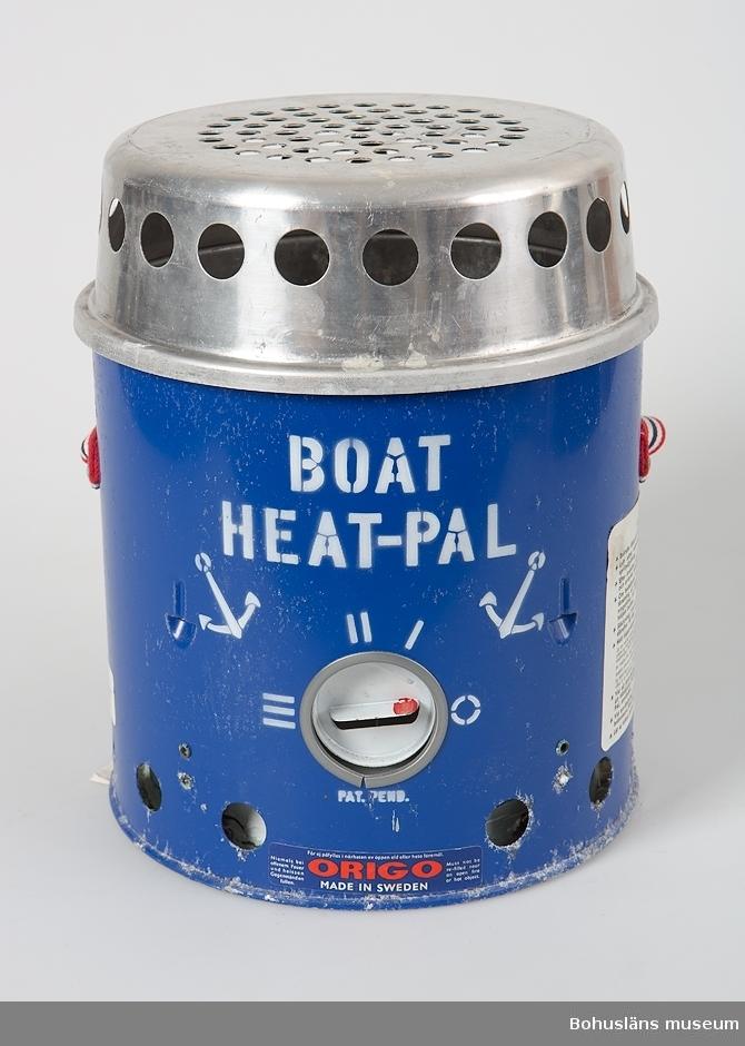 """Rund kamin, värmare  av märket """"BOAT HEAT-PAL"""".Underdel av blålackerad metall med brännre för blåsprit eller T-sprit. Överdel med genombruten skyddskåpa. Genom att lyfta av överdelen kan värmaren även användas som ett litet kök för ett kärl på gallret. Bärrem av kraftigt vävt band i rött-vitt och blått. Fastkklistrade etiektter med instruktioner och säkerhetsföreskrifter Korroderad."""