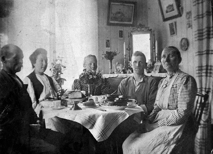 """Enl. tidigare noteringar: """"Simon Anderssons familj runt kaffebord. """"Familjen på Koö"""".  Repro 1985 av fotografi tillhörande Gustav Rundberg, Bovallstrand""""."""