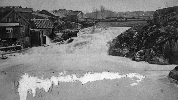 """Enligt text på fotot: """"Vattenfallet och qvarnen vid Strömberget Uddevalla, med spången före branden 1886 taget 1867. Nils fädernehem""""."""