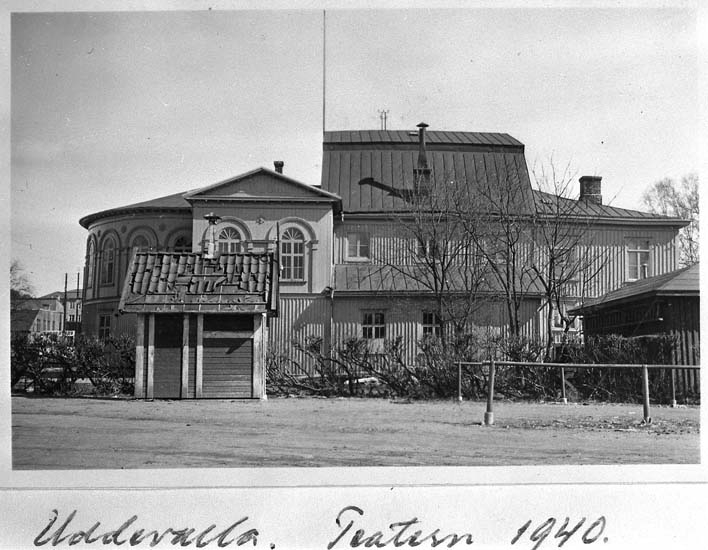 """Text på kortet: """"Uddevalla Teater 1940. Obs! Bekvämlighetsinrättningen för marknadsbesökare. Från väster""""."""