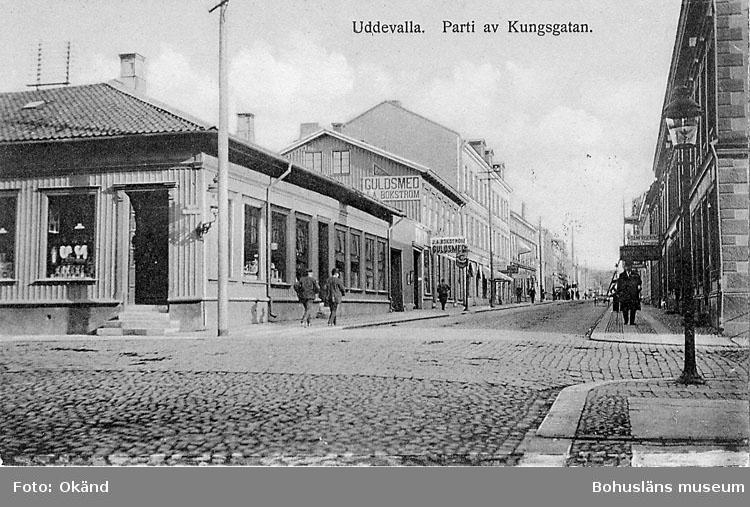 """Tryckt text på vykortets framsida: """"Uddevalla parti av Kungsgatan"""".  ::"""