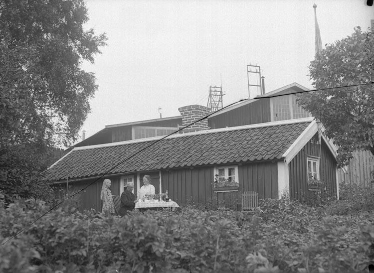"""Enligt fotografens noteringar: """"Paret J. Rundqvist. En mycket gammal stuga som troligen stått där före fabriken- det sägs att arbetare som byggde fabriken lagade sin mat där, med hjälp af en kvinna! S. Sahlberg."""""""