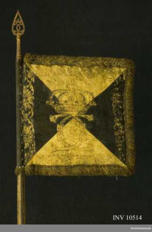 Grupp B I. Tillverkad av Balzar Friedrich 1678 i Stockholm. Duk av sidendamast, dubbel, fodrad med grovt lärft, fyrstyckad gult och svart och med målade emblem. På inre sidan Karl XI:s namnchiffer, dubbla C, rikt sirade, under sluten kunglig krona.  Bokstäver i guld med skuggning i brunt, kronan i guld med  pärlor i silver och röda och gröna stenar. Längs kanten en bård  bildad av stiliserade bladverk, kronor och palmkvistar. På yttre sidan Västergötlands sköldemärke: ett upprättstående lejon följt av tvenne sexuddiga stjärnor. Övre delen brunskuggat guld, nedre delen svart - grå på den svarta duken. Stjärnor i guld. Längs kanten samma bård som på inre sidan.  Kantad med tjock frans i gult och svart silke med insprängda  guldtrådar, fransens bredd 50 mm. Fäst på stången med tre rader förgyllda tännlikor.Stång av furu med fyra breda räfflor och förstärkt med fyra järnskenor. Löpande bärring på karbinstång av järn. Målad svart med gula refflor och handgrepp. Längd i greppet 220 mm, till duken 1490 mm. Diameter upptill 33 mm, nedom duken 42 mm, ovan  greppet 63 mm och i greppet 55 mm. Spets av förgylld mässing. Bladet genombrutet med samma  namnchiffer som på duken, endast mer stiliserat.