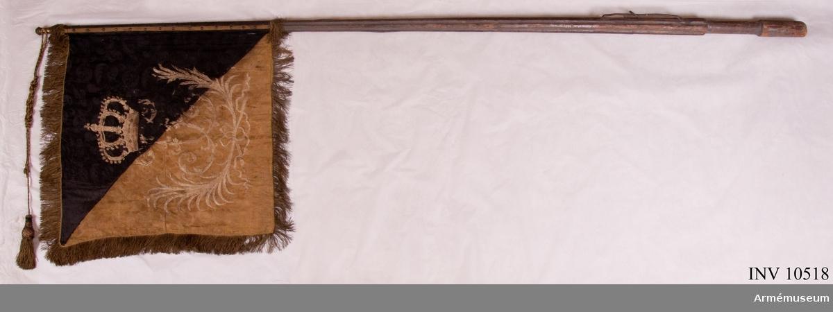 Grupp B I. Livstandar för Västgöta tre- och femmänningekavalleriregemente 1700. Cederström nr 64. Duk av vit sidendamast, med målade emblem, omvänt lika på båda sidor: i övre inre hörnet Västergötlands sköldemärke: ett upprätt lejon, övre halvan i guld, nedre i svart, följt av två sexuddiga gyllene stjärnor. Runt kanten en frans , 6 cm bred, av vitt silke. Fäst vid stången med tre vita sidenband och tre rader förgyllda tännikor. Stång av furu, vitmålad, sexrefflad och förstärkt med tre järnskenor, löpande bärring på karbinstång av järn. Längd: till greppet 0,89 m, greppet 0,19 m, till duken 1,31 m och total 2,98 m. Diameter: upptill 2,6 cm, nedom duken 3,9 cm, ovan greppet 6,6 cm och i greppet 5,1 cm. Doppsko av järn. Spets av förgylld mässing. Holken 6 cm hög. Litteratur: Cederström nr 64. Standaret bör ha förts av Västgöta tre- och femmänningar under översten Gustav Fredrik Lewenhaupt. Det har varit regementets livstandar. Förfärdigat efter Karl XII:s förordning av 17000802.