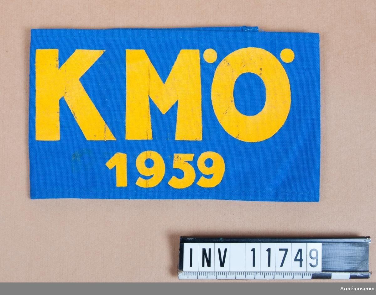 """Grupp C I. Armbindel med beteckning  """"KMÖ 1959"""". Armbindeln utdelad till inbjudna åskådare vid Krigsmaktövningar 1959 i Östergötland av Försvarsstaben. Gåva från rikshemvärnschefen generalmajor Per Kellin."""