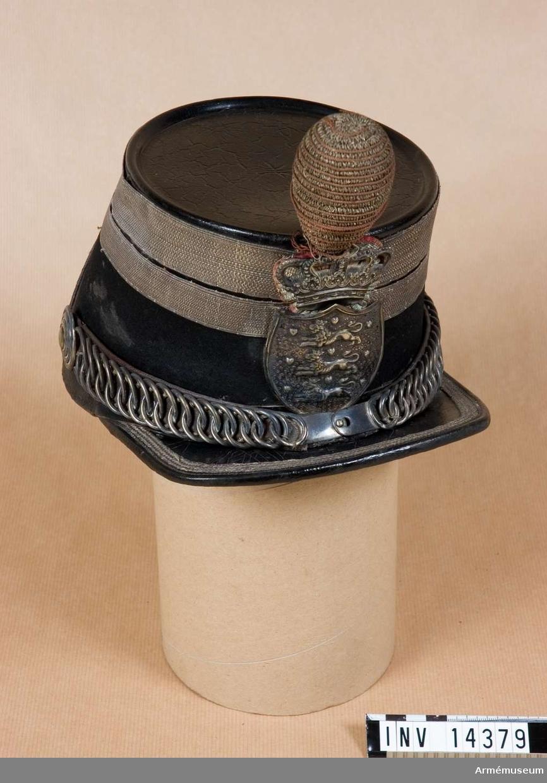 """Grupp C I. Betäckt runt om m svart kläde, på botten svart läder. Vid nedre kanten en remsa av svart läder, b: 20 mm. Vid övre kant 2 silvergaloner, den övre b: 25 mm, den nedre b: 20 mm. På baksidan en halvrund, svart läderbit m silvergalon och knapp. Framskärm av svart läder, fyrkantig, rak och m silvergalon. På skärmens baksida en papperslapp m skrift """"Militaer Gendarmer C 1890"""". Foder av svart läder. Svettrem, b: 50 mm, av svart läder. Hakremmar av svart läder m kätting och spänne av vit metall. Knäppes t käppin m knappar av vit metall. Snodd av guld och röd silkestråd m rosett på H sida. Knäppes t mössan m 2 krokar av mässing, på framsidan, ovanpå skärmen. Vapenplåt i form av sköld m danska statsvapnet, tre lejon m krona ovanpå, av gulmetall. Bakom kronan kokard av vita och röda band =danska nationalfärgerna. Pompong av röd och silverfärgad tråd, päronform, m hållare av järntråd. Enl pappersetikett från Töjhusmuseet tillhör huvudbonaden """"Feltgendarmeri, Officer käppi 1885"""" LITT  Danske Uniformer fra Haer og Flaade, tegnede af Rs Christiansen, Köbenhavn. Bild av """"Underkorpral af Feltgendarmeriet - Feltdragt"""". Gendarm i samma modell käppi m snodd på framsidan.Enl Granberg."""