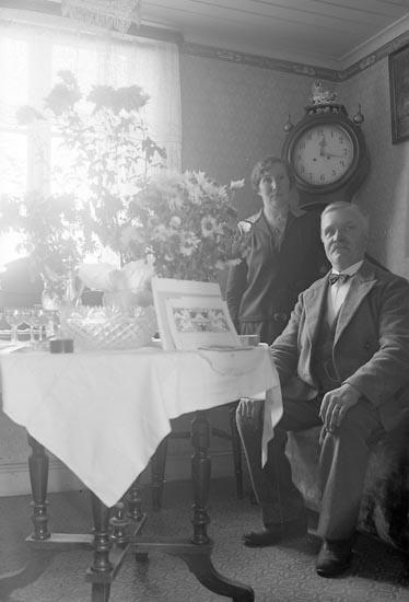 Man och kvinna poserar framför fotografen i en vrå av finrummet.