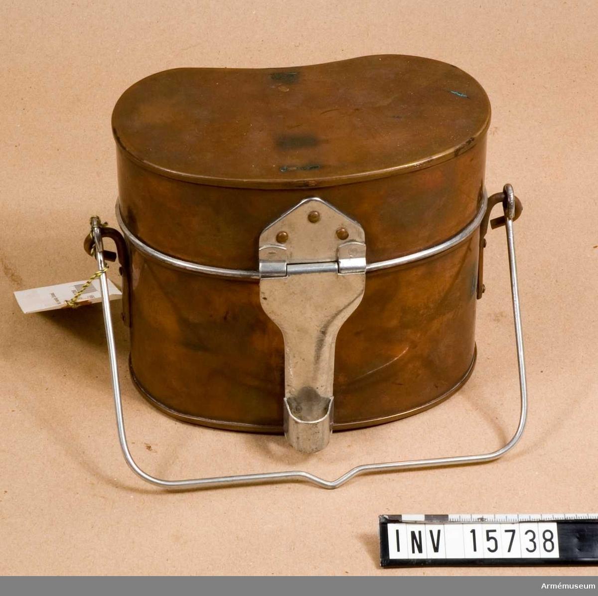 """Ur uniform.Kokkärl, manskap, Estland.Grupp C I.Kokkärl med lock (som också är panna) av kopparplåt. Kokkärl i oval form, 15 cm hög med handtag av järntråd. På sidan finns ingravering """"1 1/2"""" och """"1/2"""" rymd i liter. Lock (panna) med handtaget av järnplåt. Med detta handtag stänges kärlet tätt med lock.Tillståndet 1957-04 gott."""